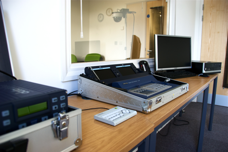 Electronic and computer equipment on a desk, behind a semi transparent glass showing another room with a video camera.