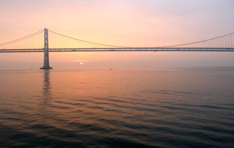A photo of a sunrise on water with the Bay Bridge in contre-jour.