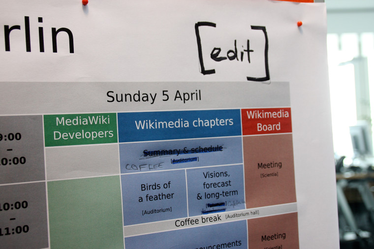 Part of a big paper schedule, on which an edit button has been written between brackets, to mimick Wikipedia's edit button