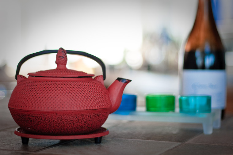 A red japanese teapot in the foreground on the left, colored glasses and a bottle in the blurry background on the right