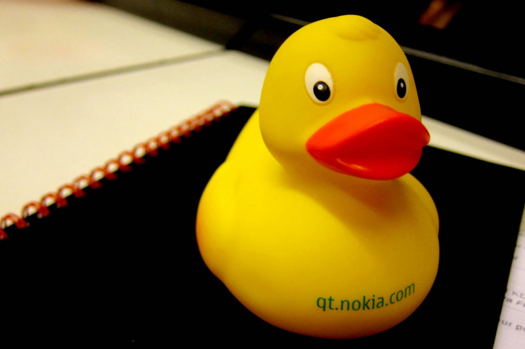 Close-up on a yellow rubber duck, sitting on on a black notebook
