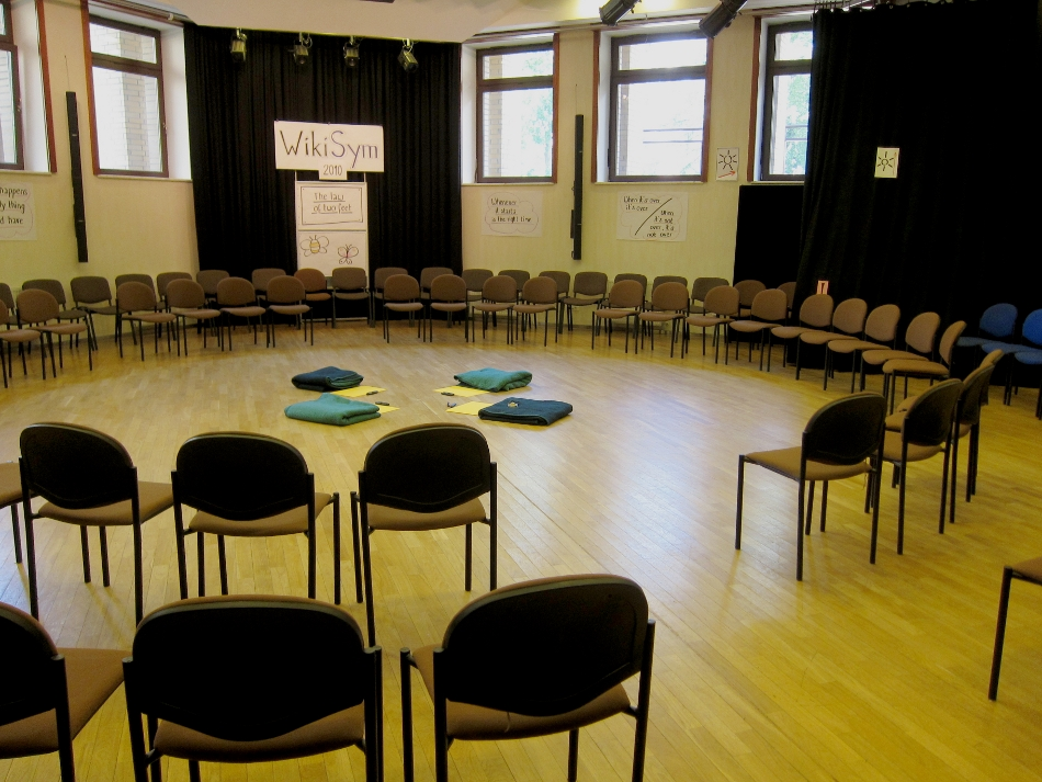 A large room with wooden floor, and a few dozen chairs assembled in a circle with several rows
